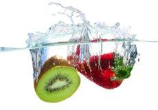 Frutas que salpican el agua Imagenes de archivo