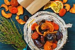 Frutas secadas en cuenco de mimbre en el fondo azul, brezo, bolsa de papel Fotografía de archivo libre de regalías