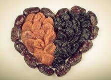 Frutas secadas, fechas, albaricoques, pasas bajo la forma de corazón en el li Imagen de archivo