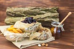 Frutas secadas y mezcla sana orgánica nuts con la miel en fondo rústico Imágenes de archivo libres de regalías