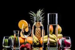 Frutas tropicales a través de la cristalería por completo del agua Fotos de archivo libres de regalías