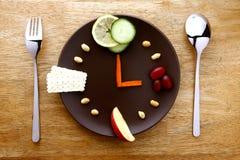 Frutas, verduras, nueces y galletas en una placa Imagenes de archivo