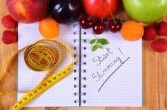 Frutas, verduras y centímetro con el cuaderno, adelgazar y comida sana Foto de archivo libre de regalías