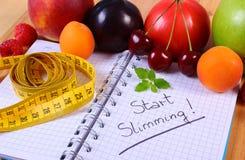 Frutas, verduras y centímetro con el cuaderno, adelgazar y comida sana Foto de archivo