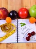 Frutas, verduras y centímetro con el cuaderno, adelgazar y comida sana Imagen de archivo libre de regalías