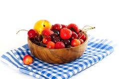 Frutas y bayas en un cuenco de madera en una servilleta a cuadros Imagenes de archivo