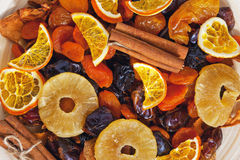 Frutas y canela secados en una placa de madera Imagenes de archivo
