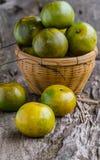 Frutas y cesta anaranjadas en fondo de madera Fotos de archivo libres de regalías