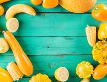 Frutas y verduras amarillas en un fondo de madera de la turquesa Imagenes de archivo