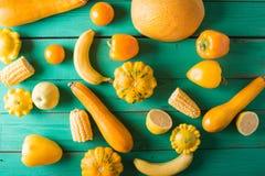 Frutas y verduras amarillas en un fondo de madera de la turquesa Fotografía de archivo