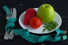 Frutas y verduras en la placa con la cinta métrica en el fondo de madera Imágenes de archivo libres de regalías