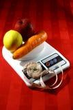 Frutas y verduras en una balanza con una cinta métrica Fotos de archivo libres de regalías