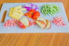 Frutas y verduras frescas coloridas en la tabla de cortar Imagen de archivo