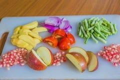 Frutas y verduras frescas coloridas en la tabla de cortar Foto de archivo