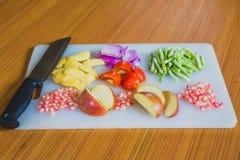 Frutas y verduras frescas coloridas en la tabla de cortar Fotografía de archivo libre de regalías