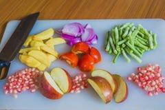 Frutas y verduras frescas coloridas en la tabla de cortar Imagenes de archivo