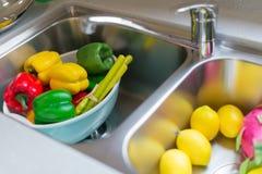 Frutas y verduras maduras simuladas en fregadero foto de archivo