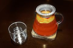 Frutifica o chá vermelho em um bule transparente com um vidro imagem de stock royalty free