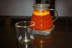 Frutifica o chá vermelho em um bule transparente com um vidro imagens de stock