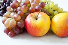 Frutifica a vista macro uvas vermelhas, amarelas das maçãs, as verdes e as violetas em um fundo branco Fotografia de Stock