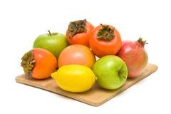 Frutifique em uma placa de corte de madeira no fundo branco Fotografia de Stock Royalty Free