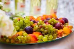 Frutifique em uma placa, em uvas, em ameixas e em pêssegos Bufete, abastecendo Fotos de Stock Royalty Free