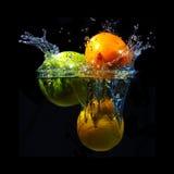 Fruto colorido que cai na água no fundo preto Foto de Stock