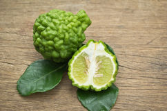 Fruto da bergamota com as folhas verdes no fundo de madeira fotografia de stock royalty free