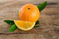 Fruto das laranjas com as folhas no fundo de madeira Imagem de Stock Royalty Free