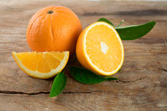 Fruto das laranjas com as folhas no fundo de madeira Fotografia de Stock Royalty Free