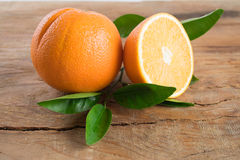 Fruto das laranjas com as folhas no fundo de madeira Foto de Stock