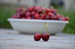 Fruto de duas cerejas em muitos cereja no fundo da bacia imagens de stock royalty free