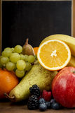 Fruto de Frash, laranja, maçã, banana, pera, uvas contra o quadro-negro Imagens de Stock Royalty Free