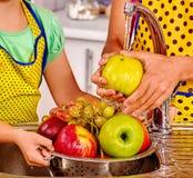 Fruto de lavagem da mulher na cozinha imagem de stock royalty free