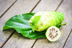 Fruto de Noni e fatia do noni na licença na tabela de madeira Fotos de Stock
