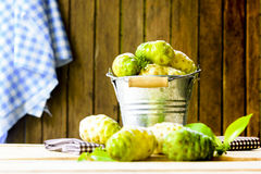 Fruto de Noni na cubeta do zinco e noni na tabela e no fundo de madeira velho Fotografia de Stock