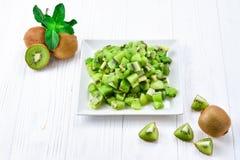 Fruto de quivi recentemente cortado com os quivis inteiros no fundo Imagem de Stock Royalty Free