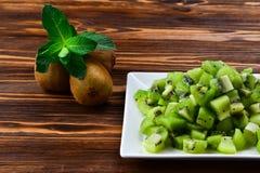 Fruto de quivi recentemente cortado com os quivis inteiros no fundo Foto de Stock Royalty Free