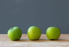 Fruto de três maçãs na tabela Foto de Stock Royalty Free