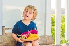 Fruto e manga cortados do dragão nas mãos do menino imagem de stock royalty free