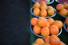 Fruto fresco de laranjas coloridas brilhantes em umas bacias com fundo escuro imagens de stock royalty free