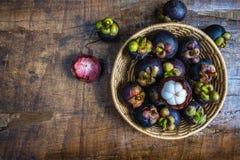 Fruto fresco do mangustão em uma cesta na tabela foto de stock royalty free