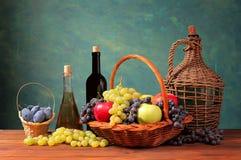 Fruto fresco em uma cesta de vime e garrafa do vinho Fotos de Stock
