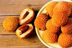 fruto Lichi-delicioso, perfumado, exótico em um fundo de madeira O lichi tem uma grande fonte de nutrientes úteis É usado dentro fotos de stock