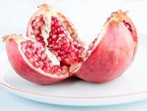 Fruto maduro da romã em uma placa branca da porcelana Fotografia de Stock Royalty Free
