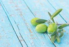 Fruto mediterrâneo da azeitona verde no ramo com as folhas na luz - fundo de madeira azul da tabela Imagens de Stock Royalty Free