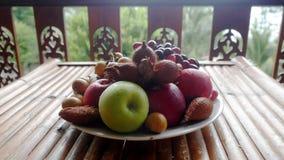 Fruto tropical delicioso e arranjado na bacia em uma tabela de madeira imagem de stock