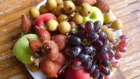 Fruto tropical delicioso e arranjado na bacia em uma tabela de madeira Parte superior da vista Movimento lento 1920x1080 filme