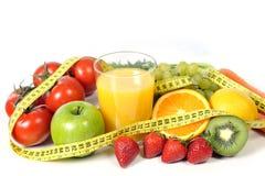 Fruto, vegetais e suco de laranja na medida da fita foto de stock