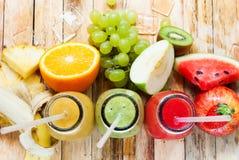 Frutos das garrafas do batido três dos sucos da fileira tropicais fotografia de stock royalty free
